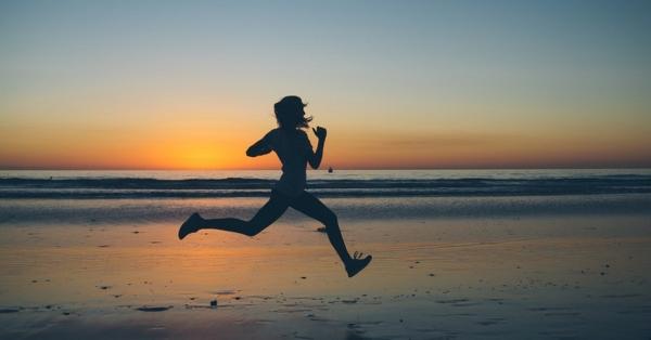 Löpning i på stranden i solnedgång