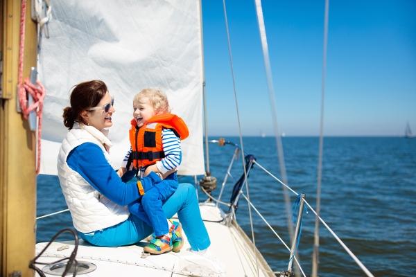 mor och barn i fören på en segelbåt