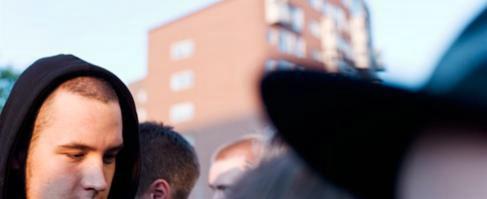 Foto.Engruppmänniskoriförgrunden,enhusfasadibakgrunden.