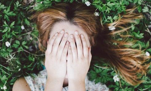 Flickasomhållerhändernaföransiktet.Bild:Scandinavsimple