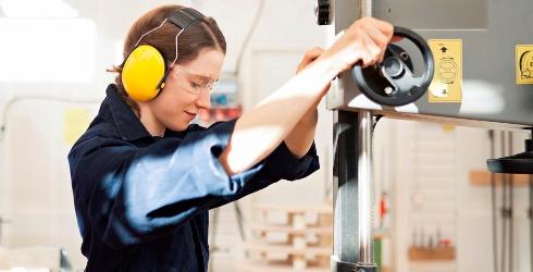 Tjej i blå overall och gula hörselskydd arbetar i verkstadsmiljö