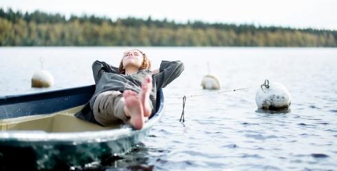 Flicka ligger och blundar i en båt vid en sjö.