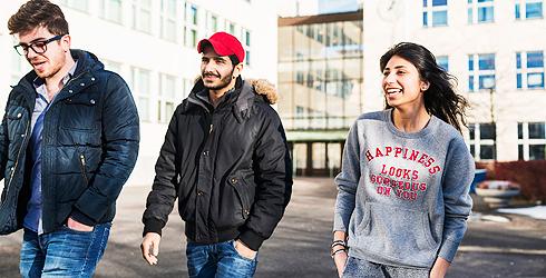 Två unga killar och en tjej på väg utanför en byggnad