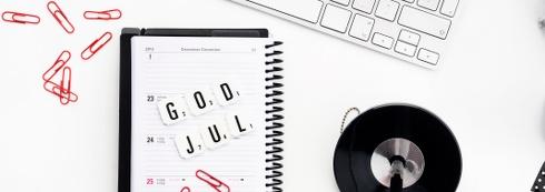 En kalender som visar julveckan med texten God jul formad av alfapet-bokstäver, röda gem, ett tangentbord och en penna