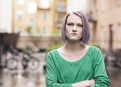 Bestämd, ung kvinna med grön tröja och lila hår och armarna i kors.