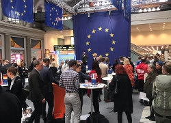 En utst�llningsyta full med m�niskor. I taket h�nger eu-flaggor
