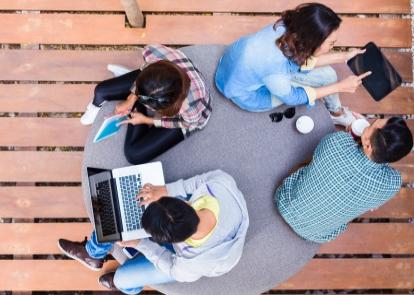 Fyra ungdomar sitter på en soffa och diskuterar, en av dem håller i en bärbar dator och en av dem har läsplatta