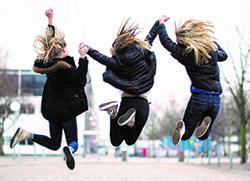 Tre ungdomar håller varandra i händerna och hoppar högt
