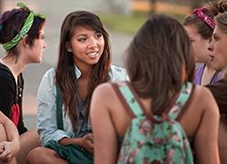 Bild på unga tjejer som sitter i en grupp och pratar. Foto: Mostphotos