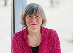 MUCF:s generaldirektör Lena Nyberg står med ryggen mot ett fönster. Hon har korslagda armar, bär en röd kofta och tittar rakt in i kameran.