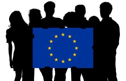 Bild p� unga m�nniskors silhuett och de h�ller i en EU-flagga Foto MRRphotography