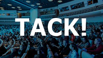 Texten TACK! p� bl�tonat foto �ver auditoriet p� rikskonferensen 2019