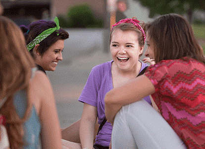 En grupp ungdomar sitter p� marken och skrattar.