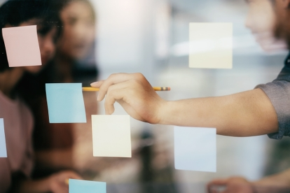 Bild p� kursdeltagare som arbetar med post-it lappar p� en glasv�gg