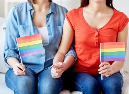 Bild på två unga hbtq-personer som håller varsin flagga i handen. Foto: Syda Productions