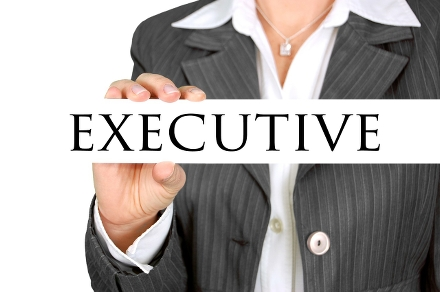 Foto av en kvinnas överkropp. Hon är klädd i grå kostym och håller upp en vit skylt som det står Executive på.
