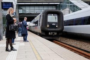 Billd på tågstation med människor och tåg