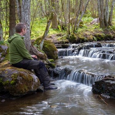 Man sitter vid mindre vattenfall i skogen. Foto: Martin Fransson.