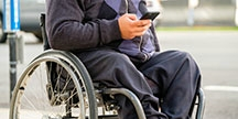 A person in a wheelchair using a smartphone. Photo