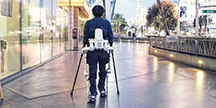 A person with robot legs and crutches. Photo