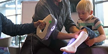 A child is testing a 3D-printed orthosis. Photo