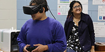 User fitted with VR goggles, headphones and a gaming controller. Photo
