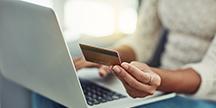En person som betaler med kort på datamaskinen. Foto