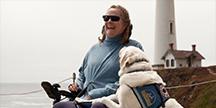 Kvinne i rullestol med førerhund. Foto