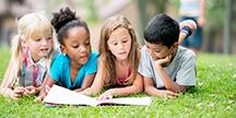 Barn som ligger på gresset og leser. Foto