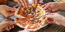 Flere personer som deler en pizza. Foto