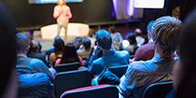 Publikum lytter til en foredragsholder. Foto