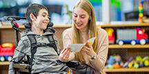 En lärare som läser för en elev i rullstol. Foto