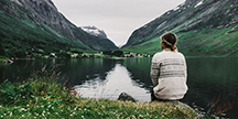 En person som sitter vid en fjällsjö. Foto