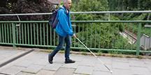 En synshemmet person som går med en hvit stokk. Foto
