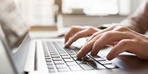 En person som bruker en datamaskin. Foto