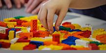 Et barn som leker med legoklosser med punktskrift. Foto