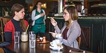 To personer som snakker tegnspråk med hverandre på en cafe. Foto