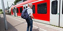 En blind person som ska stiga på ett tåg. Foto