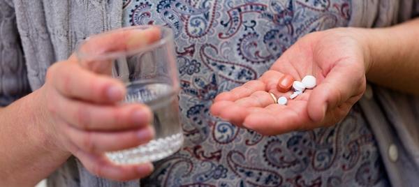 Händer som håller mediciner och ett vattenglas