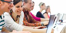 Personer i utbildning vid datorer. Foto