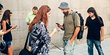 Flera personer som använder smartphones på en gata. Foto