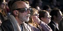 Döva personer som använder smarta glasögon vid en teaterföreställning. Foto