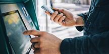 En person som använder en bankomat. Foto