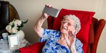 En äldre person som tar en selfie med en smartphone. Foto