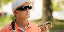 En synskadad man som använder rösten för att göra sökningar via sin smartphone. Foto