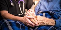 En sjuksköterska besöker en äldre patient. Foto