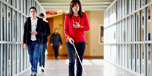Chieko Asakawa går i en korridor. Foto
