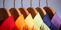 Färgglada skjortor på klädhängare. Foto