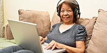 En äldre person använder en dator. Foto