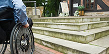 En person i rullstol vid en trappa. Foto